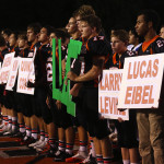 The Roseburg High School football team observes a moment of silence to recognize the nine victims of the Umpqua Community College mass shooting before a game against South Medford High School in Roseburg, Ore. on Friday Oct. 9, 2015.